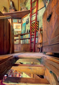 The top of Spiral Stair ascends into Esherick's bedroom (below). T he red Ladder (undated) is stored upside down to save floor space. T he Hanging Figure (1928) is used as a counterwe ight for the trap door that can close to cover the spiral stair. O n the shelf in the background are from left: Head of Dreiser (1927), Her (1942) and Owl (undated).