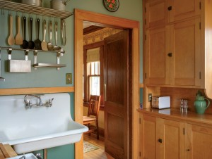 Dahl decided to keep the bungalow's original wall-mounted sink. After refinishing the kitchen cabinets, she re-installed their original latches.